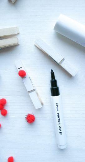 Auf der weißen Wäscheklammern wird eine rote Nase angeklebt und Augen und Mund zeichnen mit einem schwarzen Kreativmarker.