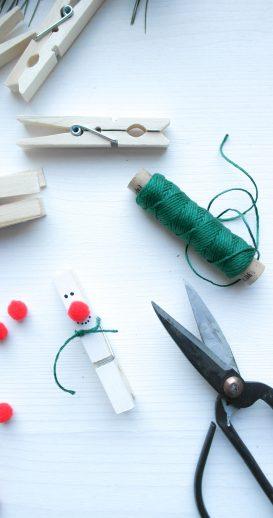 Um die Wäscheklammer wird ein Faden als Schal für den Schneemann gebunden.