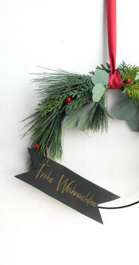"""Hängender Kranz mit einem Banner und dem Wunsch"""" Frohe Weihnachten"""""""
