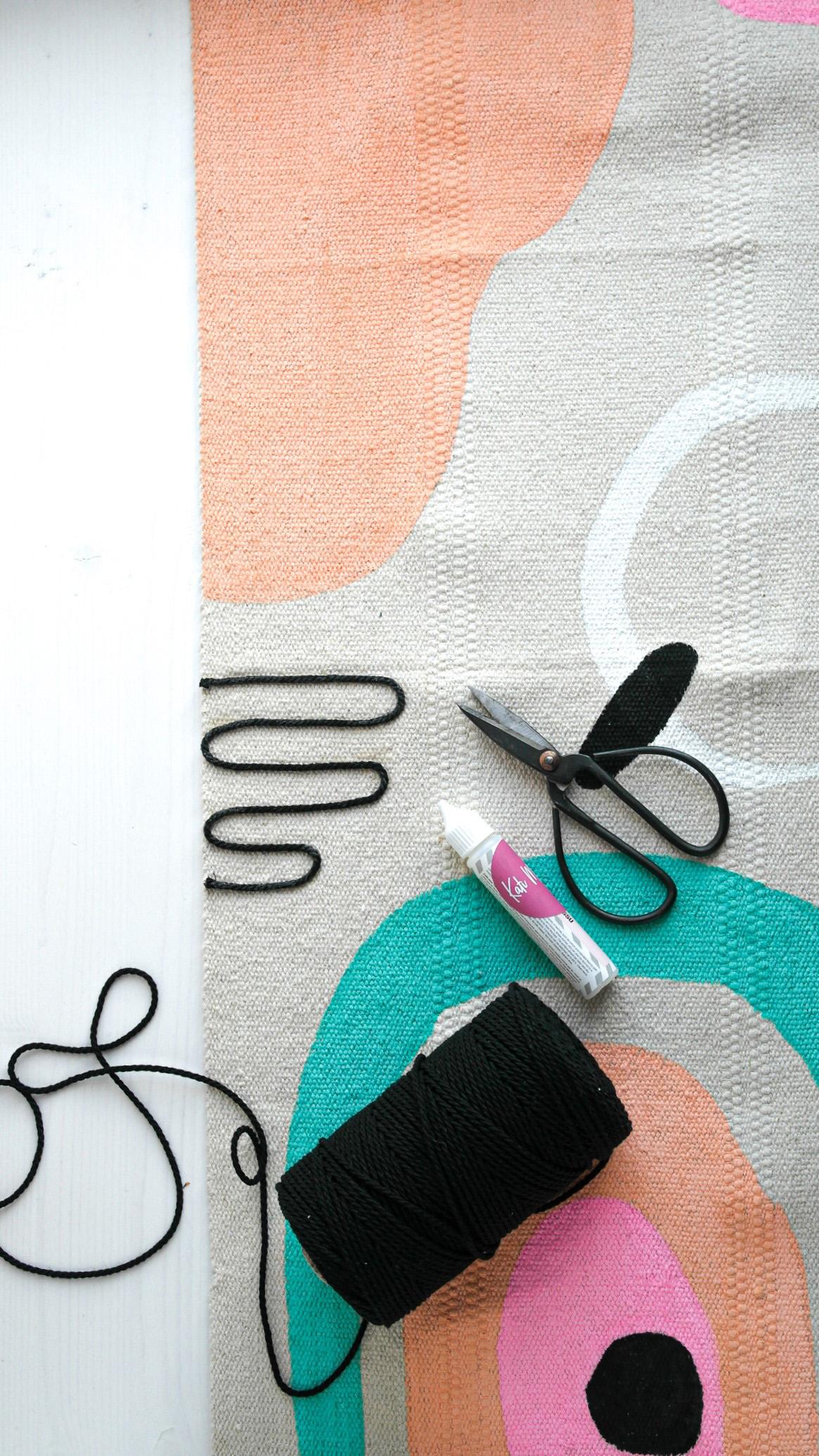 Die Wolle auf dem Teppich mit Textilkleber befestigen