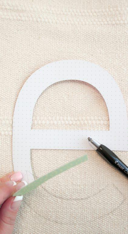 Vorlage bestehend aus Buchstaben werden auf den Teppich von Ikea Sortsö mit einem Bleistift übertragen