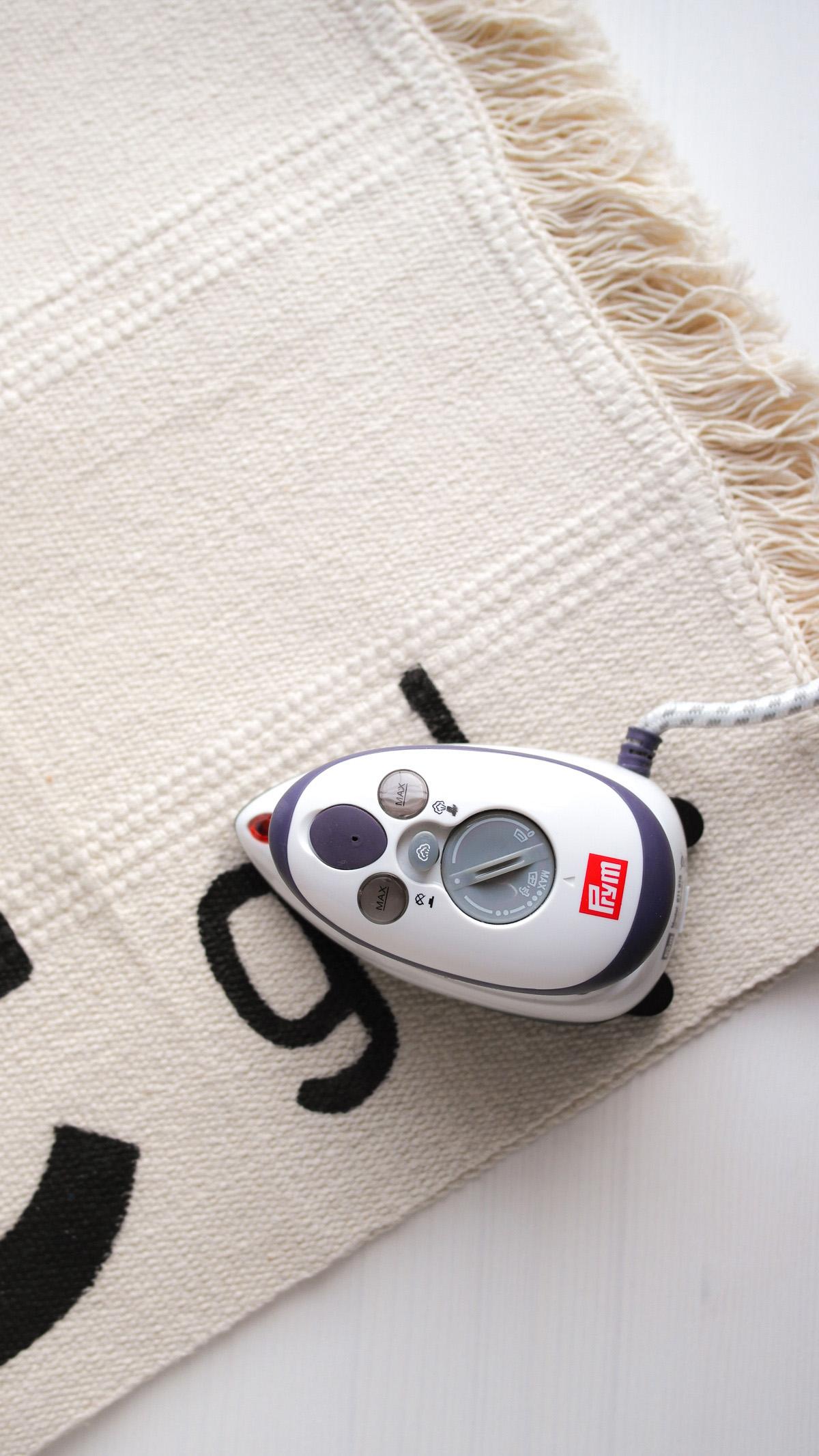 Einbügeln der Farbe auf dem Teppich Sortsö mit dem Bügeleisen